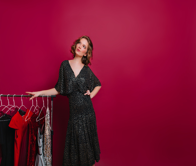 Dreamy woman in retro black dress looking up while posing beside hangers with clothes. Romantic lady with short hairstyle standing in wardrobe and thinking what to wear..